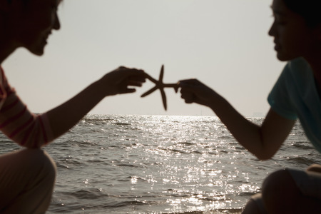 girls at the beach series: Silhouette of mother and daughter holding a starfish on the beach