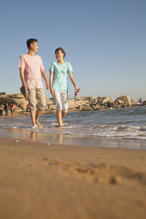 girls at the beach series: Father and Daughter walking along the waters edge, beach, China Stock Photo