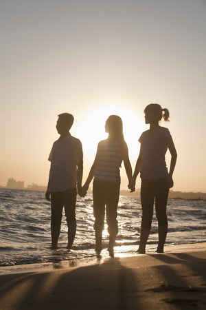 holding back: Family holding hands on the beach, sunset