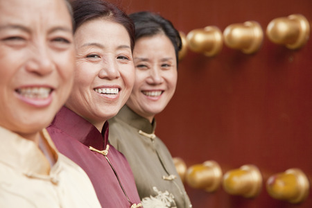 mature women: Group of mature women in traditional clothes standing next to the traditional Chinese door