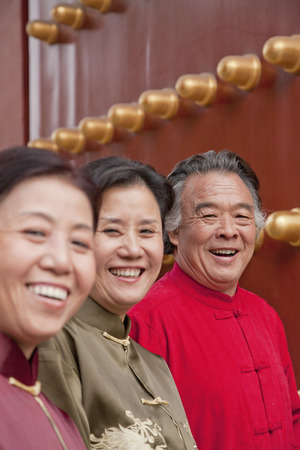 mature people: Group of mature people in traditional clothes standing next to traditional Chinese door, portrait Stock Photo