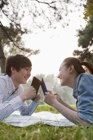 teenage couple: Teenage couple reading books in the park