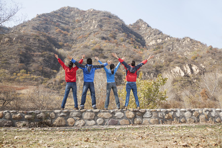 active adult community: Group of young people standing on the ledge, arms outstretched