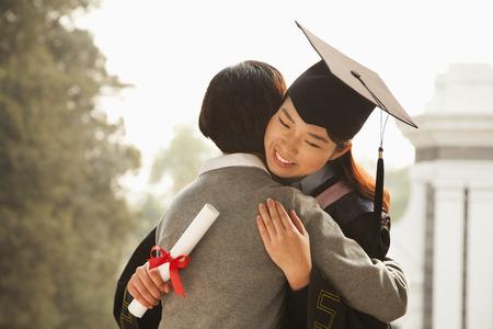 licenciado: La madre y el Graduate Abrazo