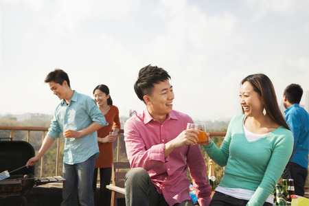 Group of Friends Having a Barbeque on a Rooftop Stock Photo