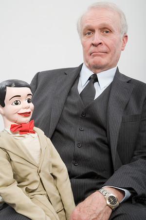 file clerk: A businessman holding a ventiloquists dummy