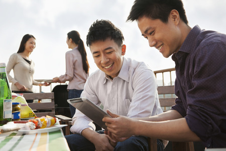 Friends Using Digital Tablet at Rooftop Barbecue Stock Photo