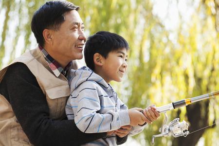 pescando: Padre e hijo juntos de pesca en el lago