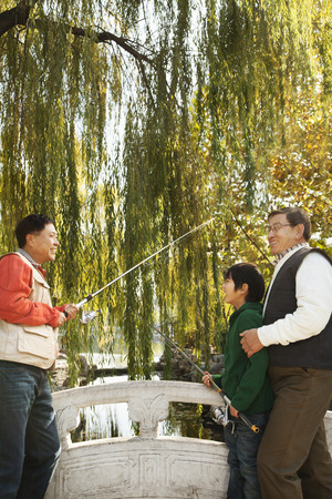 generation gap: Multi-generational men fishing at lake Stock Photo