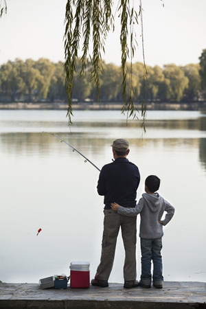 Grandfather and grandson fishing off of dock at lake photo
