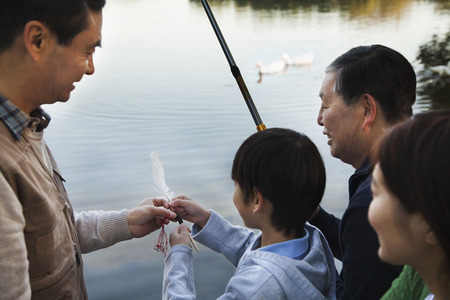 Family teaching a boy how to fish at a lake
