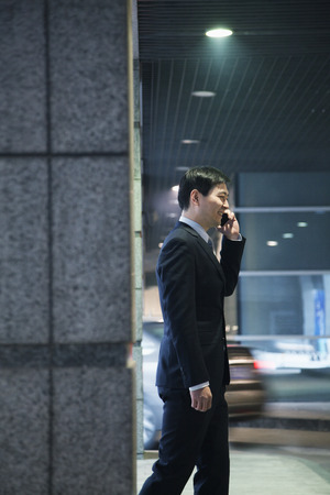parking garage: Businessman talking on the phone in a parking garage