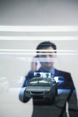 thorough: Businessman looking thorough window in parking garage, reflection of car Stock Photo