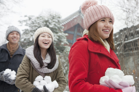 Three friends Holding snow balls in snow in park photo