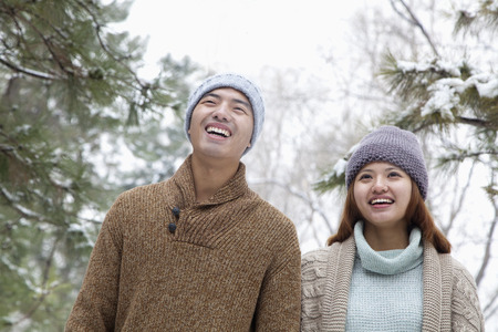 Young couple smiling in park in winter