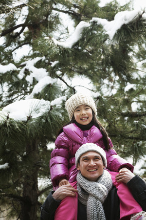 some under 18: Father and daughter under tree covered in snow