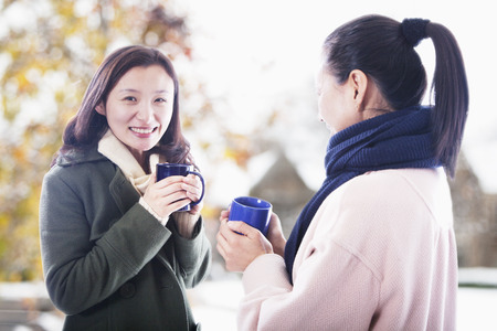 Two friends with hot beverages photo