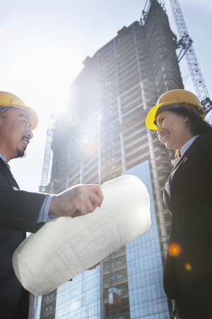 architect: Two architects at a construction site holding blueprint Stock Photo