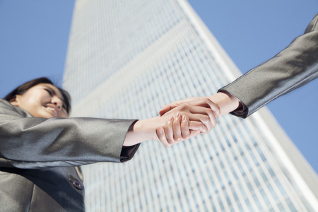 griping: Close up of two business people shaking hands by the china world trade center in Beijing