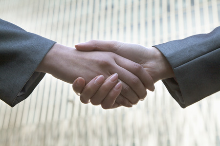 griping: Close up of two business people shaking hands by Chinas world trade center in Beijing Stock Photo