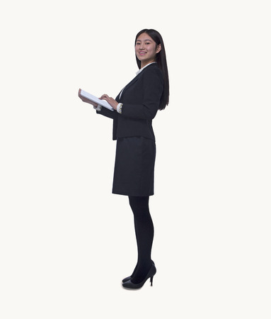 Portrait of young businesswoman holding a digital tablet, looking at camera, full length, studio shot photo