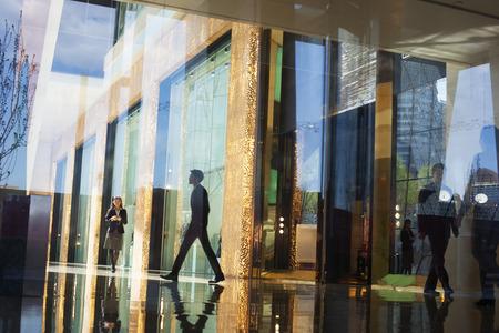 personas caminando: Hombres de negocios que recorren con el vest�bulo de un edificio de oficinas en el otro lado de una pared de cristal