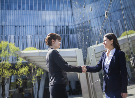 griping: Two smiling young businesswomen shaking hands outdoors in Beijing, China