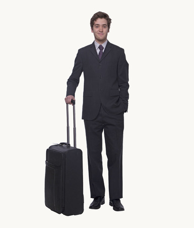 Portrait of smiling young businessman holding a suitcase, studio shot photo