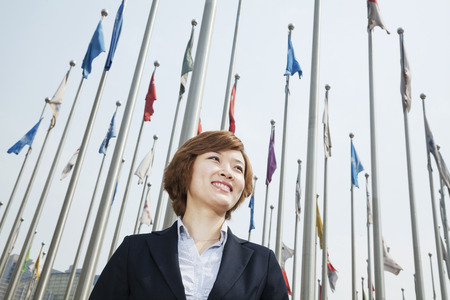 above 25: Portrait of smiling young businesswoman with flags