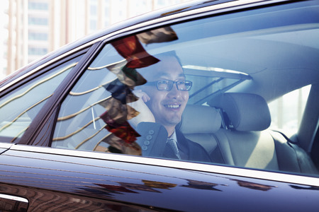 Smiling Businessman sitting in the back seat of the car photo