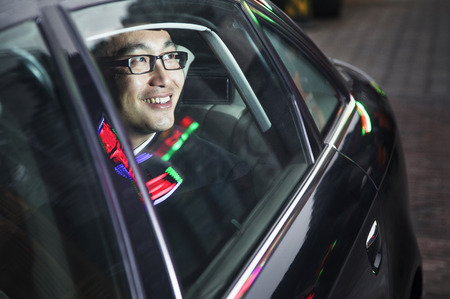 Smiling and happy businessman looking through car window at the night  photo