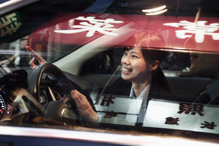Smiling businesswoman pointing out of the car while driving through Beijing at night photo