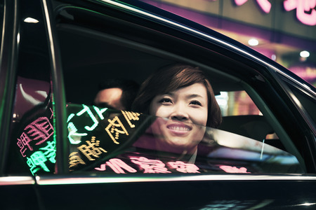 Smiling businesswoman with car window rolled down looking out at the nightlife in Beijing photo