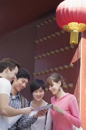 четыре человека: Four people looking at map. Фото со стока