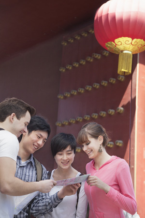 above 21: Four people looking at map. Stock Photo