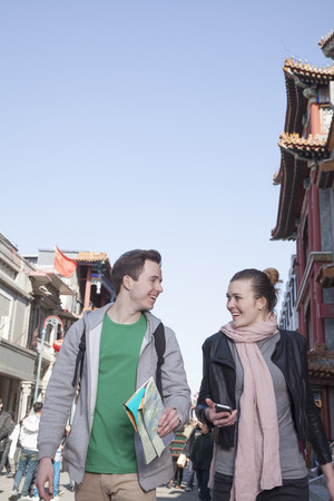 above 21: Young couple sightseeing, holding map and mobile phone.