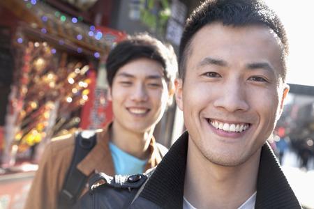 hombres jovenes: Dos hombres j�venes con la arquitectura china en el fondo.