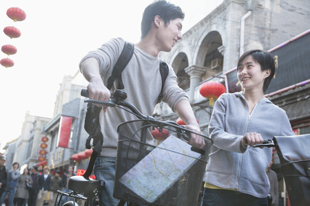 above 21: Young man and woman with bicycles and map. Stock Photo