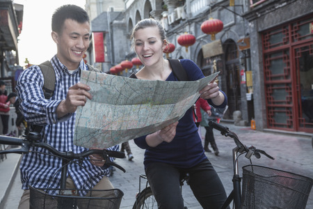 Young man and woman on bicycles, looking at map. Stock Photo