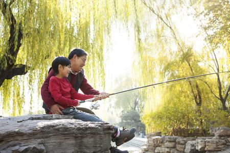 Grandfather and grandson fishing portrait at lake Banco de Imagens