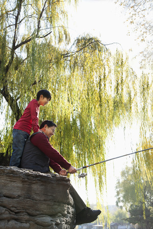 full willow: Grandfather and grandson fishing portrait at lake Stock Photo
