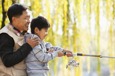 generation gap: Father and son fishing together at lake