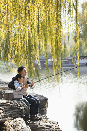full willow: Father and son fishing together at lake