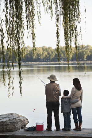 generation gap: Family fishing off a dock at lake Stock Photo