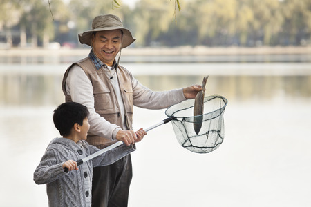 generation gap: Grandfather and grandson putting fish into net at lake