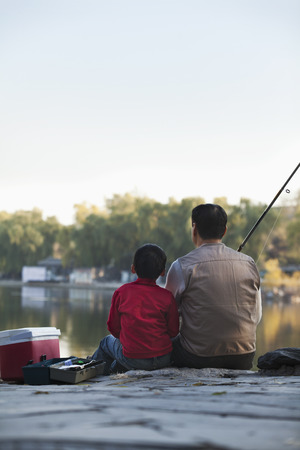 Grandfather and grandson sitting and fishing at a lake photo