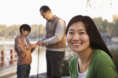 Portrait of mother with family fishing at a lake photo