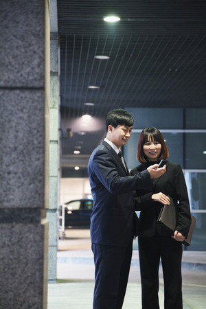 parking garage: Two business people looking at phone in a parking garage, Beijing Stock Photo