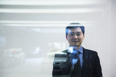 Businessman looking thorough window in parking garage photo