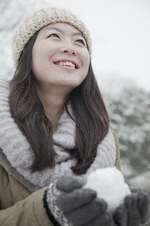 snowball: Woman Holding snowball outside in park Stock Photo